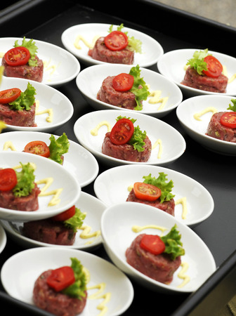 Individual servings of beef tartare topped with fresh tomato and lettuce and drizzled with mayonnaise arranged on a tray on a buffet table at a catered event