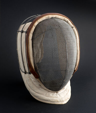 fencers: Fencing mask with the traditional fine wire mesh covering to protect the fencers face isolated on a black background