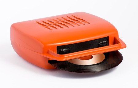 Retro orange portable record player for listening to vinyl records with a record inserted in the slot lying on a white background