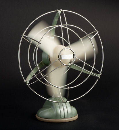 airflow: Vintage tabletop electric fan with a wire cage protecting the spinning blades creating a cooling airflow, on a black background