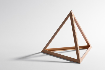 Open empty wooden triangular frame or pyramid shape forming a standard geometric triangle casting a shadow on a white background
