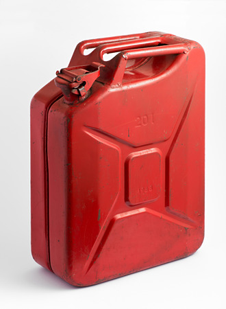 Red metal fuel tank or jerry can for transporting and storing gasoline or diesel fuel on a white background