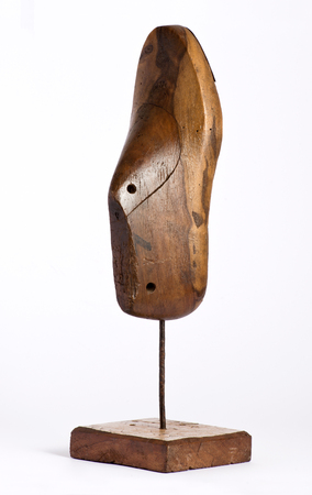 Vintage wooden shoe form or last on an upright stand used by shoemakers when manufacturing or repairing shoes on a white background