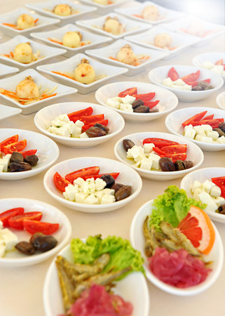 Individual cold salads and appetizers laid out on a buffet table at a catered event, rows running diagonally