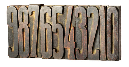 Set of old metal printers blocks for setting type with numbers 0 through 9 arranged in descending order left to right isolated on white