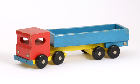 Retro wooden toy truck in a simple rustic design painted in red, blue and yellow with an open flatbed, wheels and an articulated front cab on a white background photo