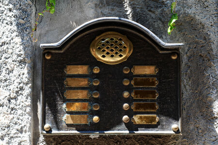 intercommunication: Brass intercom plate at an entrance to a property or building with nameplates and buttons to communicate with the owners Stock Photo