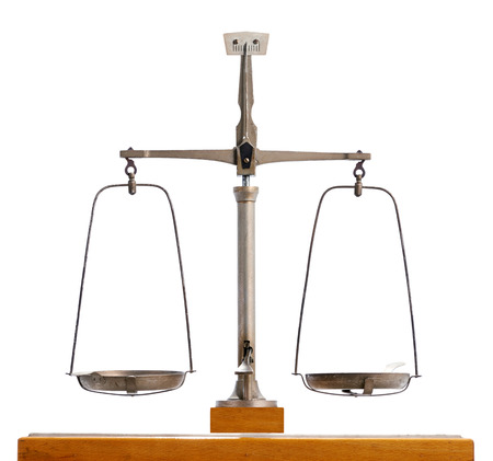 Vintage metal pendulum scale with the two empty pans balanced in equilibrium isolated on white, symbolic of justice and equality