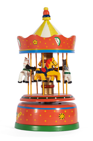 Colorful vintage red metal mechanical toy carousel or merry-go-round with horses depicting a fairground ride isolated on white Stock Photo