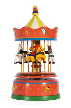 Metal rojo carrusel de juguete de colores de la vendimia mec�nica o merry-go-round con los caballos que representan una atracci�n de feria aislado en blanco