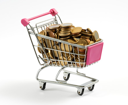 Supermarket shopping cart full of gold coins conceptual of an expensive purchase or inflation and e-commerce, on white photo