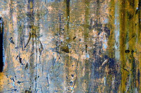 scored: Old grungy weathered metal background tetxure with a mottled pattern of blue green and pink paint remnants scored by deep scratches