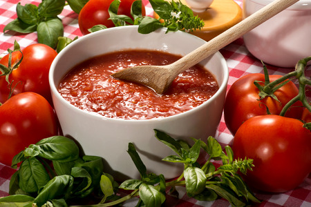 Bowl of fresh healthy homemade tomato puree with a wooden spoon for use in Italian cuisine surrounded by fresh basil for seasoning and ripe red tomatoes