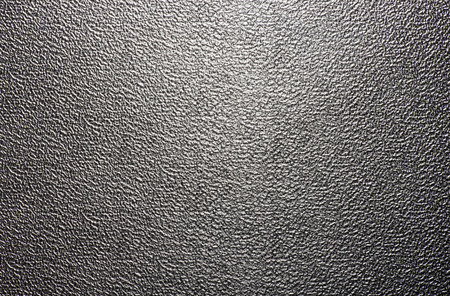 stippled: Background texture of a shiny metal sheet with a rough stippled textured surface reflecting light Stock Photo