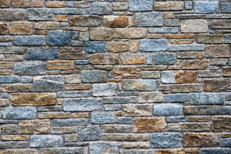 greys: Architectural background of a natural stone wall with irregular sized rectangular cut stone bricks in a range of muted greys and browns with a rough surface texture
