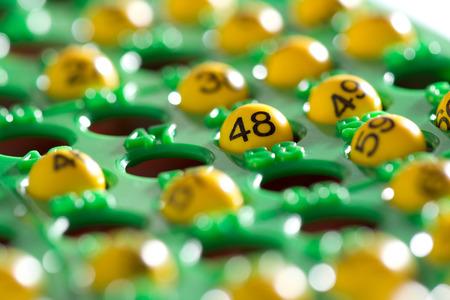 Colorful tablero del bingo verde medio lleno de n�meros de la suerte en bolas de pl�stico de color amarillo durante un juego de bingo, vista de �ngulo bajo, con especial atenci�n al n�mero 48 Foto de archivo
