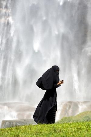 burka: Donna islamica vestita in un burka pieno in piedi sul prato verde con uno smartphone, vista laterale con copyspace sopra