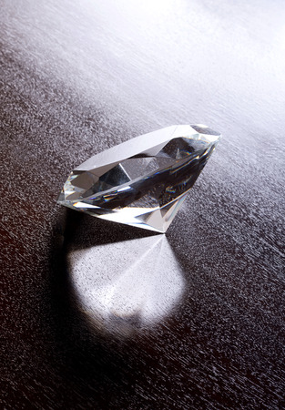 Still Life of Large Shiny Diamond Shot from Above on Wood Grain Background