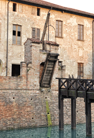 Old wooden drawbridge on a medieval castle wall in the upright position preventing people from entering by crossing the moat Éditoriale