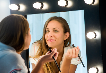 mirror: Attractive young woman applying her makeup reflected in a mirror with a light bulb surround looking at the camera with a friendly smile Stock Photo