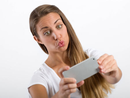 puckering lips: Young woman puckering up for a selfie pursing her lips as though requesting a kiss as she poses in front of her mobile phone Stock Photo