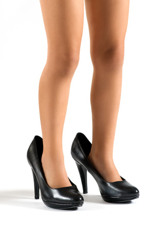 Close up view of the legs of a little girl wearing her mothers classic black high heeled shoes several sizes too big for her, over white photo