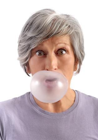 Mujer adulta a corto Cabello gris Blowing chicle con los ojos abiertos mirando a c�mara. Aislado en el fondo blanco.