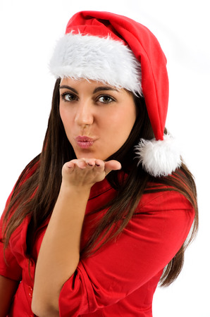 Attractive sexy young woman in a Santa hat blowing a kiss across the palm of her hand as she wishes you a merry Christmas isolated on white