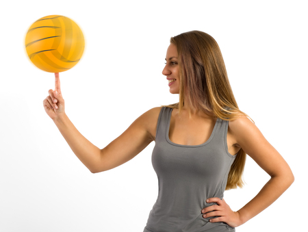 fingertip: Attractive young woman standing sideways balancing a ball on the tip of her finger her finger with a pleased smile, isolated on white Stock Photo