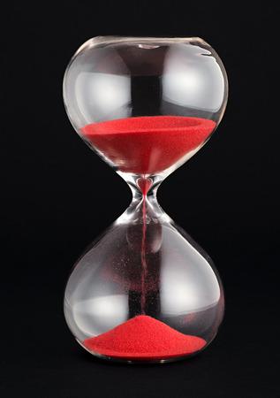 검정색 배경에 지나가는 분 또는 시간을 측정하여 잔여 시간을 세는 유리 전구를 통해 달려가는 붉은 모래 모래 시계