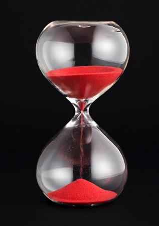 Hourglass with red sand running through the glass bulbs counting down the remaining time as it measures the passing minutes or hours, on a black background