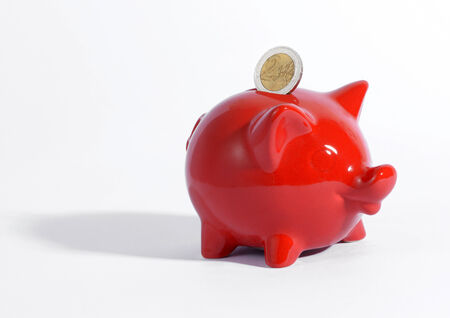 savings goals: Red ceramic piggy bank with a Euro coin suspended above the slot conceptual of success, savings, finances and investment for achieving ones goals, with copyspace