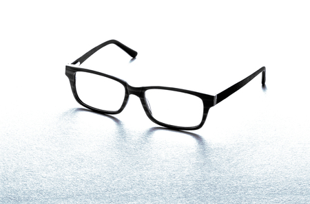 near sighted: Pair of black framed spectacles or eyeglasses for correcting defective vision or for reading on white with a reflection and copyspace