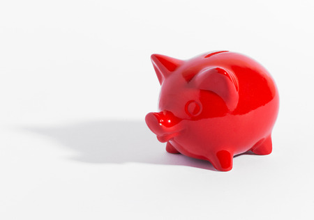 savings goals: Red ceramic piggy bank or money box on white with a shadow and copyspace in a conceptual financial image of savings and investment Stock Photo