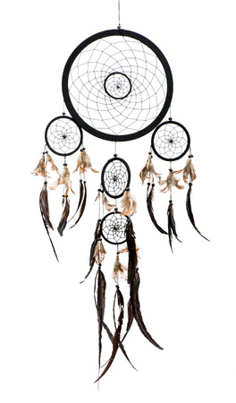 dream catcher: Native American Indian dreamcatcher with a willow hoop or circle supporting a net which filters good and bad dreams which then pass down the feathers to the sleeper, on white