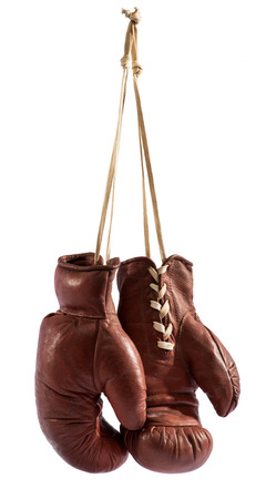 boxing equipment: Pair of vintage brown leather boxing gloves hanging from a hook by their laces, isolated on white