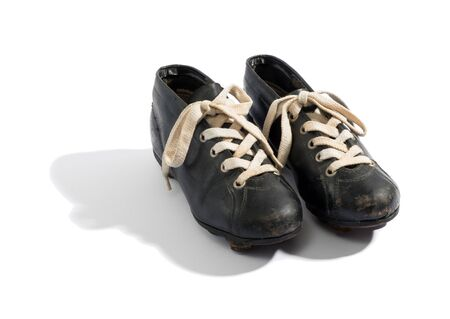 soccer boots: Pair of old black leather soccer boots with laces and a shadow displayed on a white background, high angle view