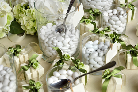 Close up White Sugared Almonds on Small Glasses and Small Gift Boxes with Green Ribbons on Top of the Table.