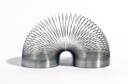 Close up Glossy Metal Spring in an Arc Position Isolated on a White Background