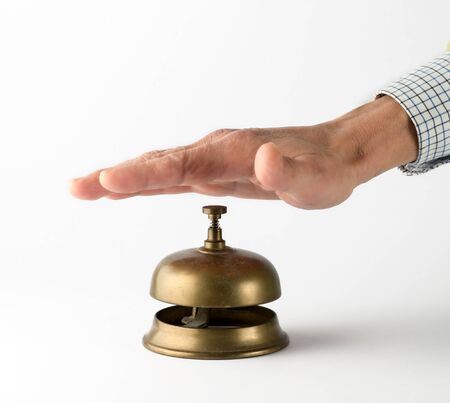 summons: Businessman Hand with Visible Shirt Sleeve Ringing Brass Service Bell on White Background Stock Photo