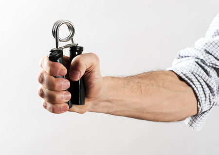 Male Hand with Rolled Up Shirt Sleeve Exercising Strength Using Hand Gripper Against White Background
