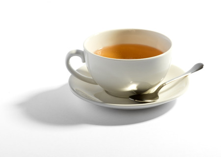 Milky tea in a white ceramic teacup with a teaspoon resting on the saucer over a white background with shadow