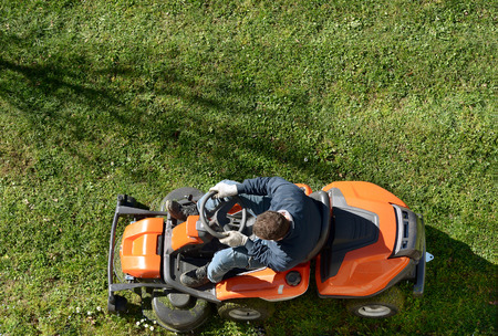 그가 마당 유지 보수에 참석할 때 오렌지 라이딩 잔디 깎는 기계에 잔디를 깎고있는 남자의 위에서 본 스톡 콘텐츠