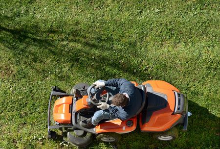 Bovenaanzicht van een man maaien een gazon op een oranje zitmaaier als hij verzorgt werfonderhoud