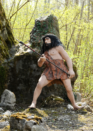 homo sapiens: Statue of a Homo Sapiens Leaning on the Boulder and Holding a Primitive Weapon Hunting Tool, Emphasizing Hunting an Animal.