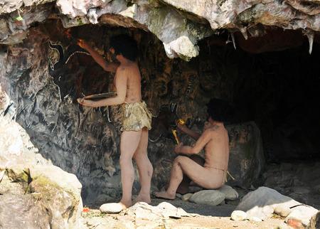 쥬라기 테마 공원 전시회 바위 동굴에서 호모 사피엔스 동굴 거주자의 선사 모델