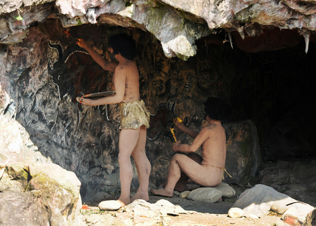 Prehistorical models of Homo sapiens cave dwellers in a rock cave at a Jurassic theme park exhibition