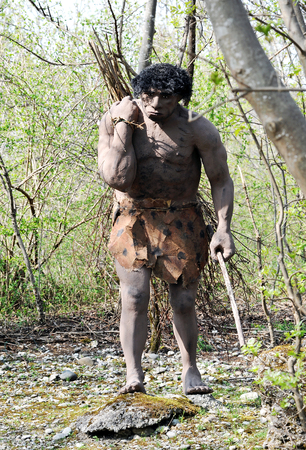 neanderthal  man: Front View of Model of Neanderthal Man, an Extinct Species of Human, Carrying Bundle of Sticks Over Shoulder in Outdoor Theme Park