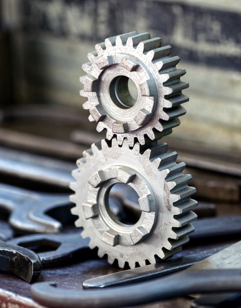 Two newly machined interlocking toothed gears in an industrial engineering workshop standing upright on a work bench