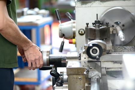 Männlich bluecollar Arbeiter machen die manuelle Arbeit mit Drehwerkzeuge Industrie-Maschine in der Metallverarbeitung verwendet Lizenzfreie Bilder